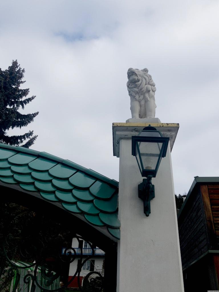 Steinerner Löwe auf einem Sockel neben einem Hauseingang