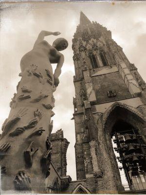 Eine Statue und der Tumr des Mahnmals St. Nikolai