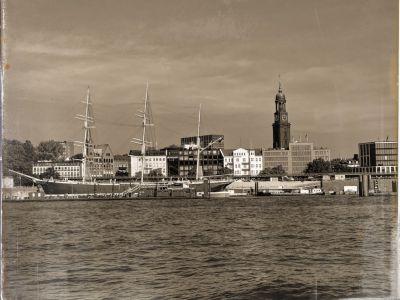 Blick von der Elbe auf die Landungbrücken mit der 3-mastigen Rickmer Rickmers und dem Michel im Hintergund