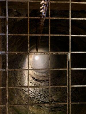 Blick durch ein Gitter in den tiefen Brunnen, der unter beletuchtet ist.