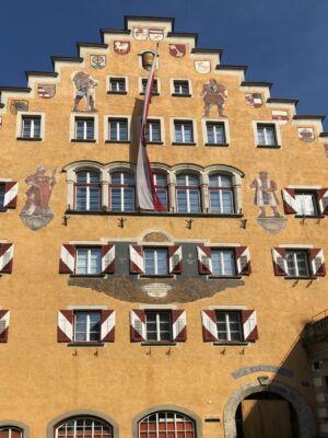 Die Fasade des Rathaus Kufstein mit Malereien und einer Tirol-Flagge