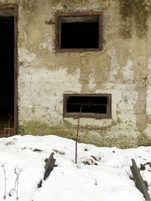 Mauer mit 2 Fenstern übereinander und das Ende von Gleisen